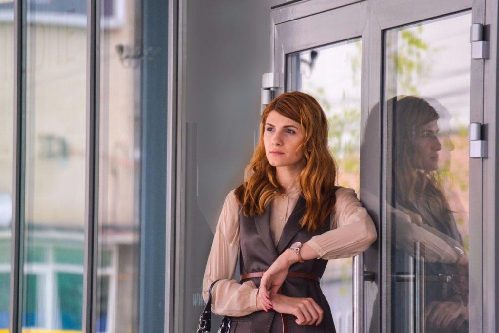 alpha woman leaning on door